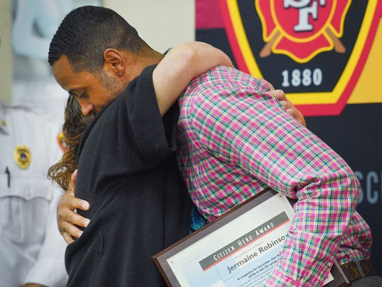 Jermaine Robinson gives Tami Crate a hug after he receives