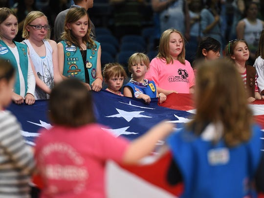 Area Girl Scouts hold the American flag for the singing of the National Anthem at a basketball game in 2015. The area council of the Girl Scouts is among the local nonprofits in the running for grants from A Community Thrives.