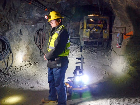 A miner is backed by a robot in the Edgar Mine near Denver, Colo., Dec. 13, 2017. The U.S. Environmental Protection Agency is considering robots and other technologies to investigate abandoned or inactive mines to learn what needs to be done with contaminated water spilling out of the mines and into rivers. Many of the mines are poorly understood and dangerous because of bad air and cave-ins. (AP Photo/Tatiana Flowers)