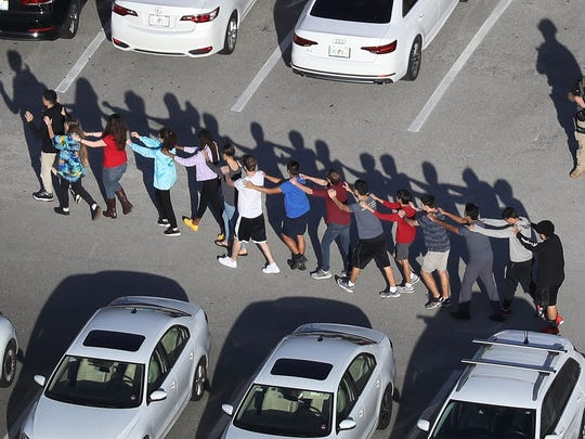 People are brought out of the Marjory Stoneman Douglas High School after a shooting at the school that reportedly killed and injured multiple people on February 14, 2018 in Parkland, FL.