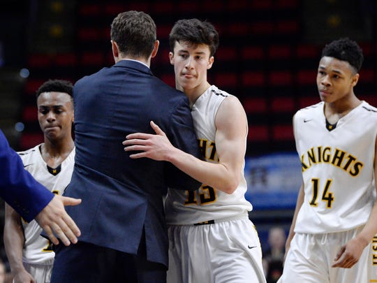 McQuaid's Josh Purcell, right, is hugged by head coach