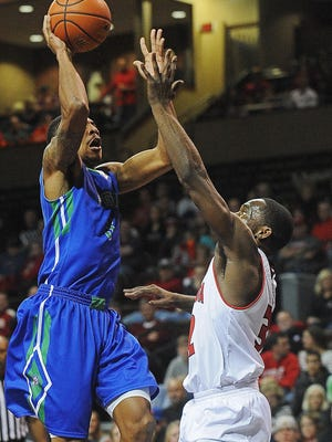Florida Golf Coast's Julian DeBose (3) goes up for a shot as USD's D.J. Davis (32) defends during a game Monday, Dec. 28, 2015, at the Sanford Pentagon in Sioux Falls.