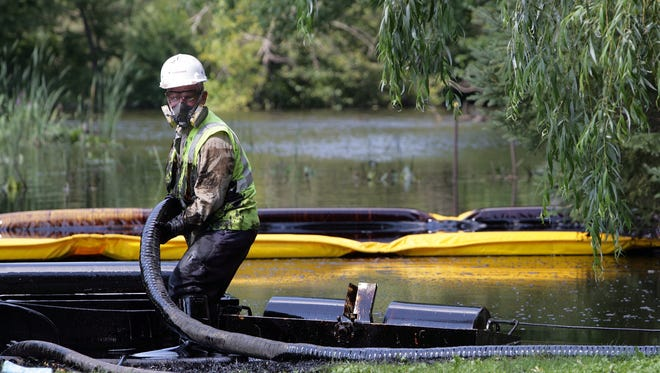 Workers from Enbridge skim oil off the surface of the Kalamazoo River on Tuesday, July 27, 2010, after a pipeline ruptured in Marshall, Mich.