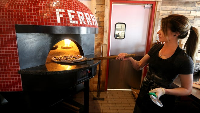 Anna Darby checks on a pizza at Ferrari Pizza Bar in Chili.  They do wood-fired pizza as well as wood-fired wings with other menu items.