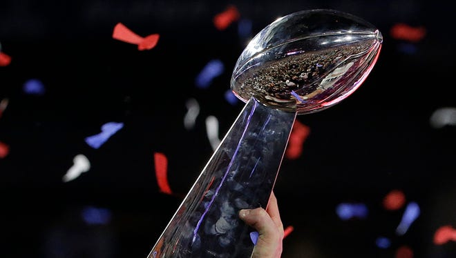 New England Patriots tight end Rob Gronkowski holds up the Vince Lombardi Trophy after the Patriots beat the Seattle Seahawks in the NFL Super Bowl XLIX football game Sunday, Feb. 1, 2015, in Glendale, Ariz. (AP Photo/Kathy Willens)