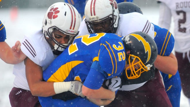 River Rouge's Stephen McGill, left, and Dontize Sims halt Ida's Eric Bugg.