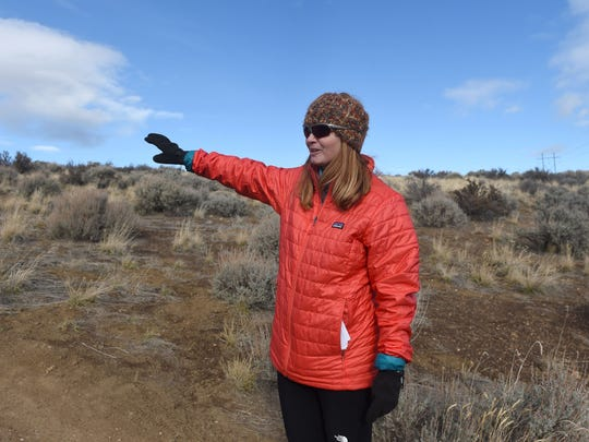 Marliee Wintz stands along the Stage Coach Trail on Peavine Peak and points to where she says she had a close call with stray gunfire during a Feb. 17 hike.