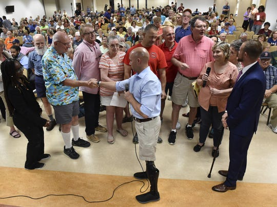 """Congressman Brian Mast (center) reaches out to Bob Fishel, USAF retired, from Stuart (second from left), while answering audience questions during his veterans town hall meeting Friday, Feb. 24, 2017, at the Havert Fenn Center in Fort Pierce. """"It's important because people know that you are listening,"""" Mast said. """"They asked me to represent them in Washington, and I can't be a good representative if I don't listen."""""""