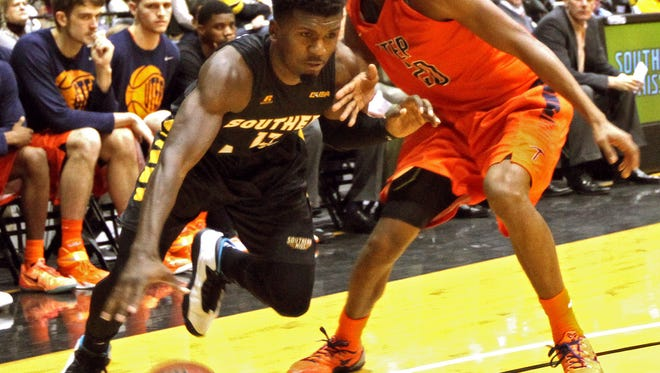 Southern Mississippi guard Chip Armelin (13) drives past UTEP guard Earvin Morris (20) during the first half of their NCAA college basketball game in Hattiesburg, Miss., Saturday, Feb. 28, 2015. (AP Photo/George Clark)
