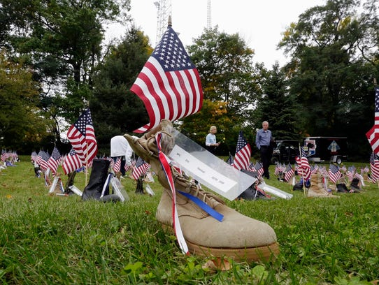 Boots representing soldiers dot the grassy area at