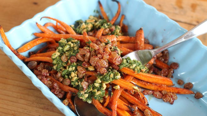 Skip the dill and butter and elevate your side dish with this recipe for roasted carrots with port raisins and spicy peanut herb sauce.