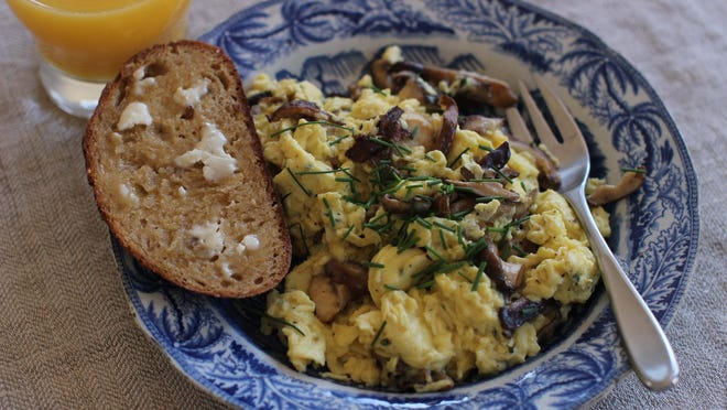 American scrambled eggs with wild mushrooms uses freshly grated Parmesan cheese and truffle oil.