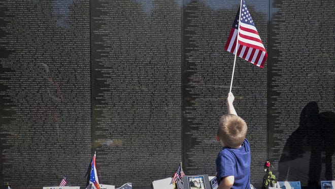 A young boy stands by the Vietnam Veterans Memorial in Washington, D.C., on the day before people across the nation honor fallen servicemembers on Memorial Day.