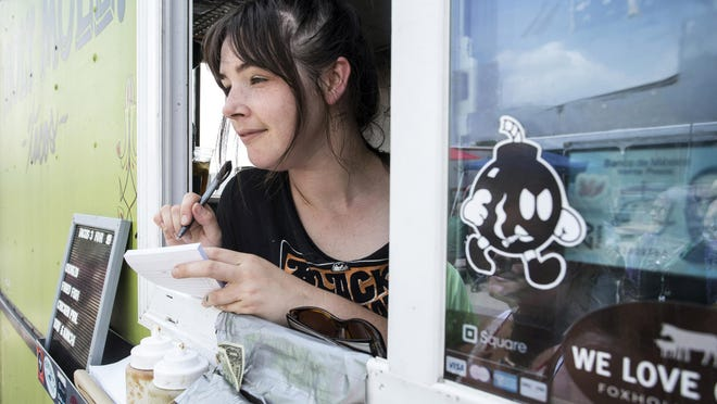 Rachel King stays busy as she mans the window of the Holy Mole Truck at the Flea Off Market on Saturday. 6/6/15