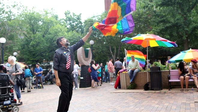 Mark McCusker of Iowa City dances on the pedestrian mall as he celebrates the U.S. Supreme Court's decision to legalize gay marriage on Friday.