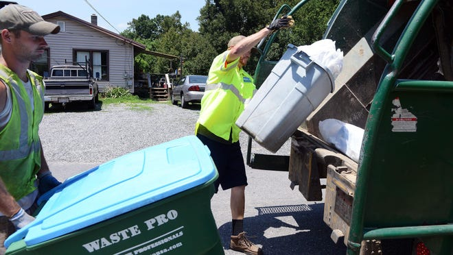 Waste Pro is offering bonuses to attract more workers, as competition for drivers and workers in general, has gotten fierce. In this file photo, Waste Pro workers Caleb Smith, left, and Lewis Knight, load trash into a truck along Jordan Road in Swannanoa.