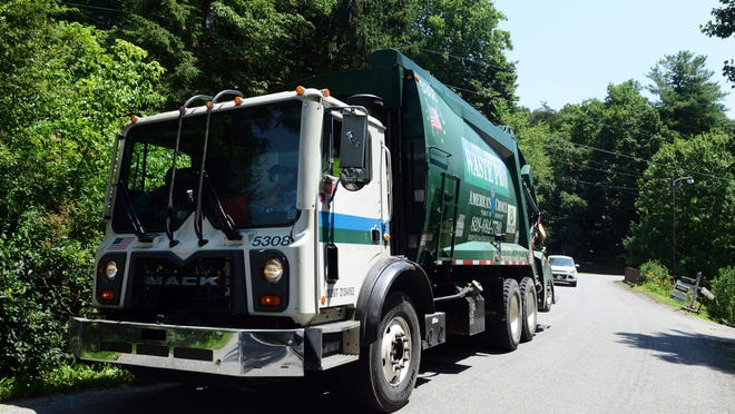A Waste Pro truck and crew works along Jordan Road in Swannanoa collecting trash Wednesday afternoon.