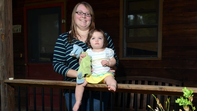 Erwin High School teacher Fallon DeMonte holds her daughter, Tessa, on the front porch of their home north of Weaverville Friday morning.