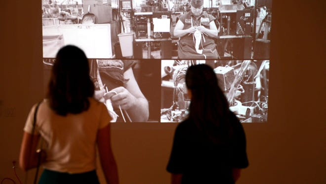 The People's Cloth Trade Show exhibition includes a video in which artist Carole Francis Lung knits a sock in front of an industrial knitting machine. During the four-hour film, Lung makes one sock whereas the machine creates almost 100.