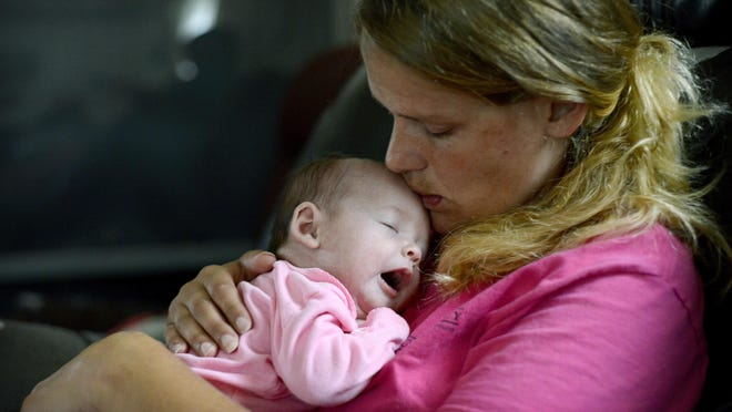 Missy Tomberlin kisses her 2-month-old baby, Maliegha Ingle, and her home in Candler on Wednesday. Tomberlin took part in the Mountain Area Health Education Center's Centering Pregnancy program. The model has inspired all types of group care at the regional medical facility.