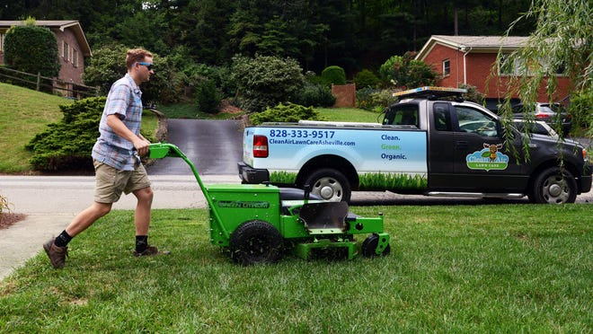 David Wood of Clean Air Lawn Care Asheville uses a solar-powered lawn mower to cut the grass at a home off Wisteria Drive in Asheville Tuesday. The truck, pictured in background, carries solar panels, attached to the roof, which can recharge the mower after each cutting. To see a video visit: citizen-times.com.