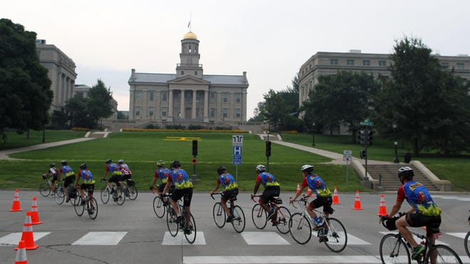 RAGBRAI cyclists pass the Old Capitol in Iowa City on Saturday, July 25, 2015.
