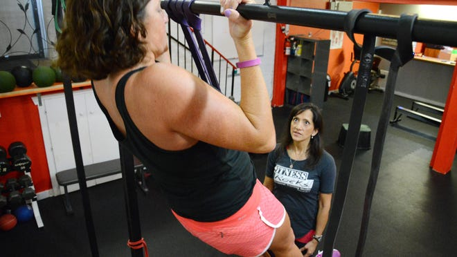 Delisa Layne of Fitness Rocks! works with Michelle Mulak of FLORIDA TODAY as she does chinups.