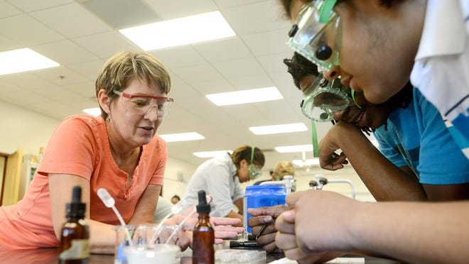 Jennifer Thomas, left, helps Jabri Black, 16, center, and Caleb Hansley, 16, right, with a lab during her chemistry class at Asheville High School on Monday. Thomas, who has been a teacher at the school for 20 years, says that she loves teaching at the school but understands that public education is not always the most attractive option for professionals who can make more money with their skills in industry jobs.