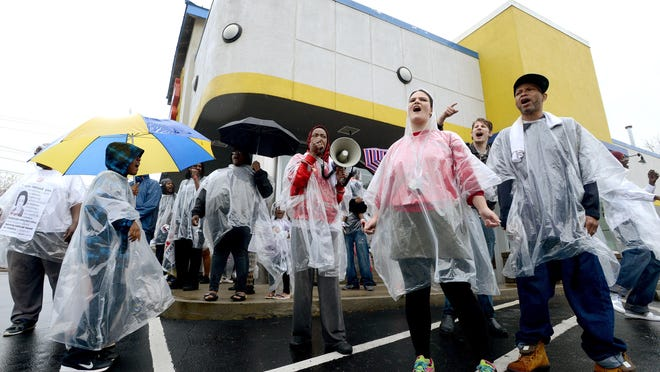 Sherricka Williams, center, leads a chant with a megaphone as Brandy Edmonds, center right, and Bobby Greenwood, far right, answer her as they protest for higher wages in front of Long John Silver's on April 15. The protest was part of Fight for 15, a national protest to raise the minimum wage to $15 per hour.