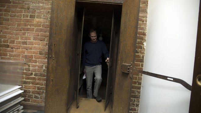 Local historian Vance Pollock checks out the steel doors of the underground vault at Pack's Tavern where legends of a tunnel used for bootlegging liquor still remain a mystery.