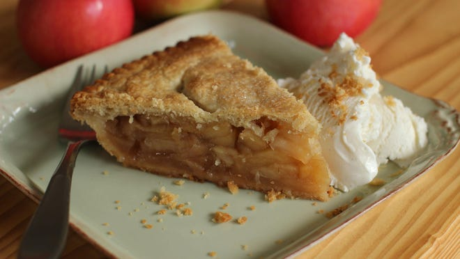 A deep dish apple pie is served with ice cream.