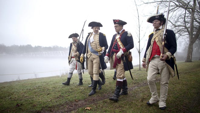 John Godzieba, second from left, portraying Gen. George Washington, walks with his troops during a re-enactment of Washington's historic crossing of the Delaware River, Friday, Dec. 25, 2015, in Washington Crossing, Pa. (AP Photo/ Joseph Kaczmarek)