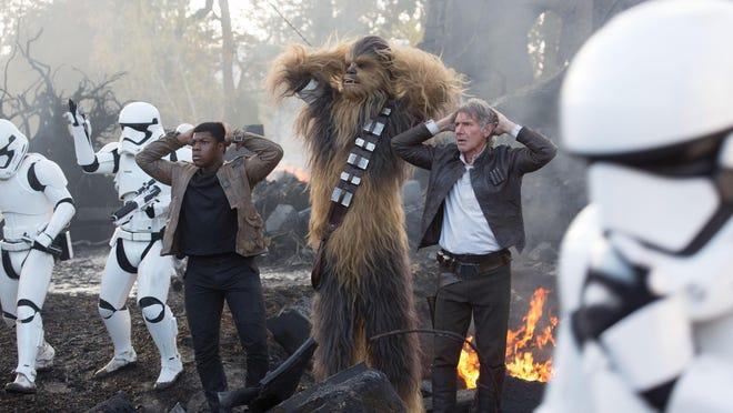 "Finn (John Boyega) joins Chewbacca (Peter Mayhew) and Han Solo (Harrison Ford) in ""Star Wars: The Force Awakens."""
