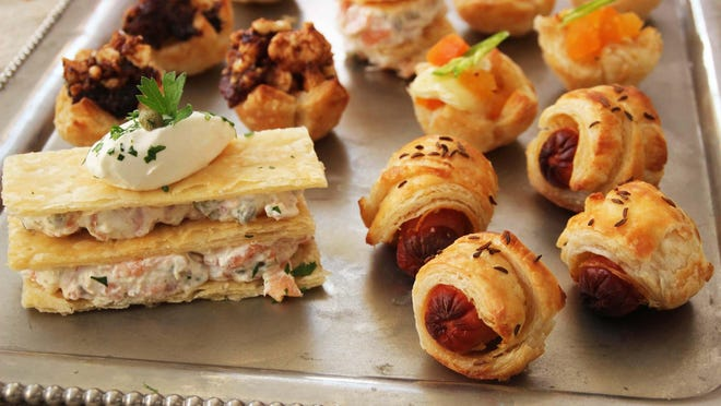 A tray of puff pastry hors d'oeuvres with, clockwise from foreground left, smoked salmon Napoleon, prune and Gorgonzola cup topped with bacon, Brie and dried apricot cup topped with Serrano chili and pigs in a blanket sprinkled with caraway seeds.