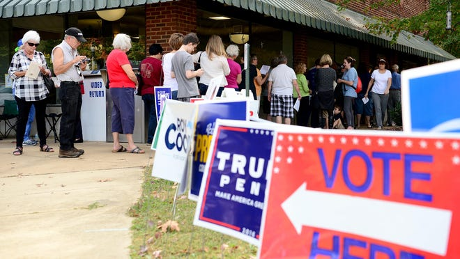 The line at the Enka-Candler Public Library wraps around the corner of the building Thursday as voters wait to cast their ballots on the first day of early voting.
