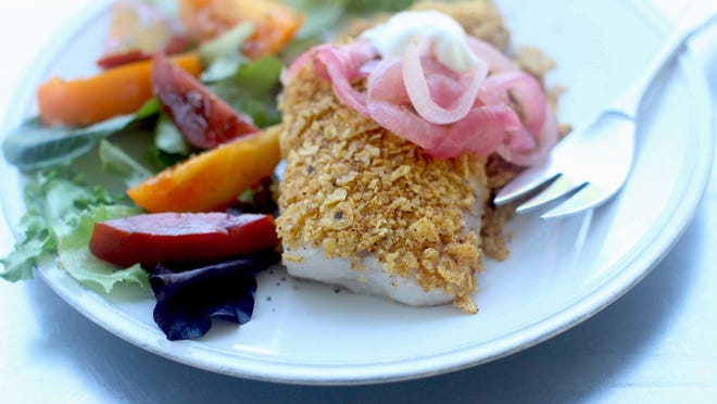 Tortilla crusted tilapia is served with pickled red onions.