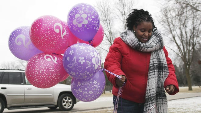 In this Jan. 27, 2017, photo, Helen Jackson brings balloons to the grave of her daughter, Cataleya Tamekia-Damiah Wimberly, at Graceland Cemetery in Milwaukee, before releasing them in honor of what would have been her 2nd birthday. Wimberly died at the age of 1 in Feb. 2016 from a methadone overdose in a case the Milwaukee police are still investigating. The number of children's deaths is still small relative to the overall toll from opioids, but toddler fatalities have climbed steadily over the last 10 years.