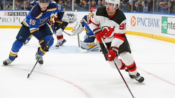 New Jersey Devils' Marcus Johansson, right, of Sweden, handles the puck as he is pressured by St. Louis Blues' Colton Parayko during the first period of an NHL hockey game Tuesday, Jan. 2, 2018, in St. Louis. (AP Photo/Billy Hurst)