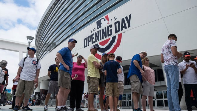 Fans wait outside the ballpark for the gates to open prior to an opening day baseball game between the Chicago Cubs and the Miami Marlins, Thursday March 29, 2018. (AP Photo/Gaston De Cardenas)