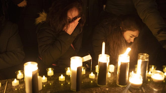 Mourners attend a vigil in Toronto, Thursday, Jan. 9, 2020, to remember the victims of the civilian Ukrainian jetliner that crashed near Tehran late Tuesday, killing all 176 people on board. (Chris Young/The Canadian Press via AP)
