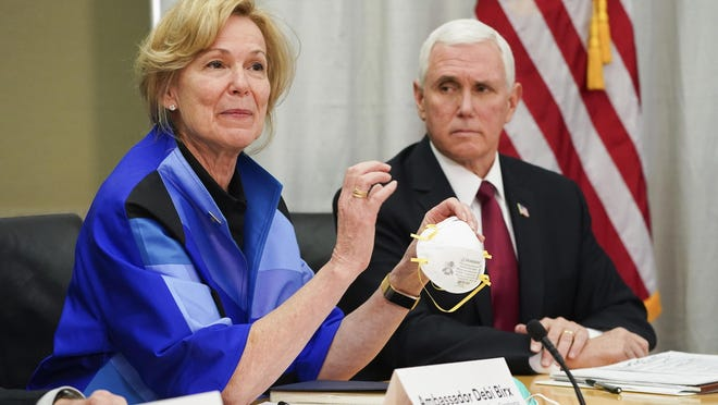 FILE - In this March 5, 2020, file photo, Dr. Deborah Birx, Ambassador and White House coronavirus response coordinator, holds a 3M N95 mask as Vice President Mike Pence visits 3M headquarters in Maplewood, Minn., in a meeting with 3M leaders and Minnesota Gov. Tim Walz to coordinate response to the COVID-19 virus. A review of federal purchasing contracts by The Associated Press shows federal agencies waited until mid-March to begin placing bulk orders of N95 respirator masks, mechanical ventilators and other equipment needed by front-line health care workers. (Glen Stubbe/Star Tribune via AP, File)