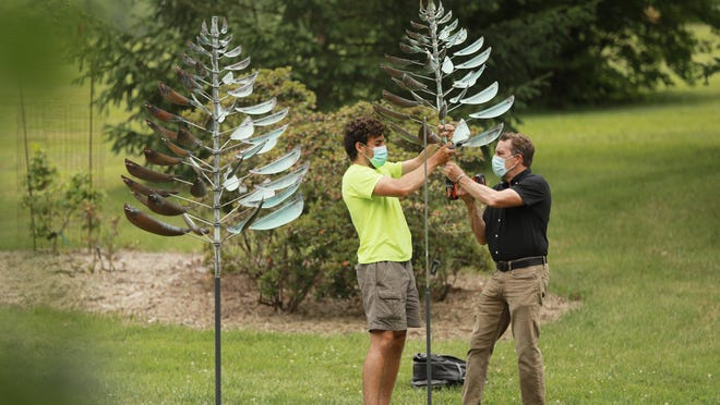 Nick Jewett, left, and Paul Dorrell install one of 60 Kinetic Wind Sculptures going up at Dawes Arboretum on Thursday. Dorrell, the president of Leopold Gallery in Kansas City, Missouri, said the pieces were created by artist Lyman Whitaker and are meant to both blend into the environment and create a contrast to the 2,000-acre Licking County site.
