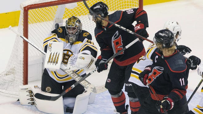 Boston Bruins goaltender Jaroslav Halak (41) eyes the puck in front of Carolina Hurricanes' Vincent Trocheck (16) as Hurricanes' Jordan Staal (11) looks on during third period on Saturday.