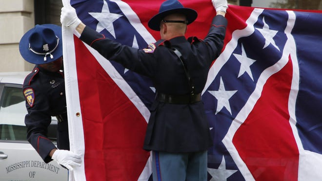 A Mississippi Highway Safety Patrol honor guard folds the retired Mississippi state flag after it was raised over the Capitol grounds one final time in Jackson, Miss., on July 1, 2020. Vestiges of the Civil War and Jim Crow segregation are coming down across the Old Confederacy as part of a national reckoning on race and white supremacy. A diversifying Democratic Party hopes the changes in symbols are part of a more fundamental shift in a region that dominated by Republicans for a generation -- and white conservative Democrats a century before that.
