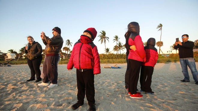 """Bundled up for warmth, beachgoers snap photos as they watch the sunrise  Sunday morning, January 5, 2020 in Lake Worth Beach. Temperatures dropped overnight and were in the upper 50s around sunrise. From left to right are Alma Marquez, Cindy Calderon (age 17), Hector Perez, Alex Perez (center, age 5), Luis Pallares, Jr. (age 10), Graciela Pallares, Emmanuel Pallares (age 5), and Luis Pallares. """"It is warm here"""" in comparison to Kansas, said Graciela Pallares. """"It is a good winter."""" Luis Pallares, Jr., Graciela Pallares, Emmanuel Pallares, and Luis Pallares are from Kansas. Alma Marquez, Hector Perez, Cindy Calderon, and Alex Perez are from Wellington."""