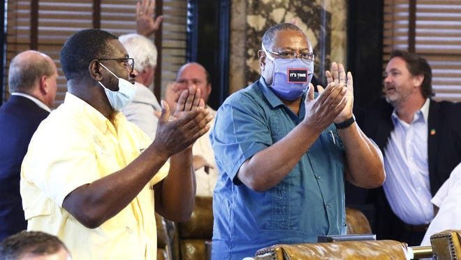 Democratic Sens. Juan Barnett, left, of Heidelberg, and Robert Jackson, of Marks, applaud while their colleagues give each other high-fives after the Mississippi Senate passed a resolution that would allow lawmakers to change the state flag, Saturday, June 27, 2020, at the Capitol in Jackson, Miss. Senators voted 36-14. Members of both the House and Senate are now expected to pass a bill that removes the current flag and establishes a path forward to getting new one. Gov. Tate Reeves has already said he would sign whatever flag bill the Legislature decides on. The current flag has in the canton portion of the banner the design of the Civil War-era Confederate battle flag, that has been the center of a long-simmering debate about its removal or replacement.