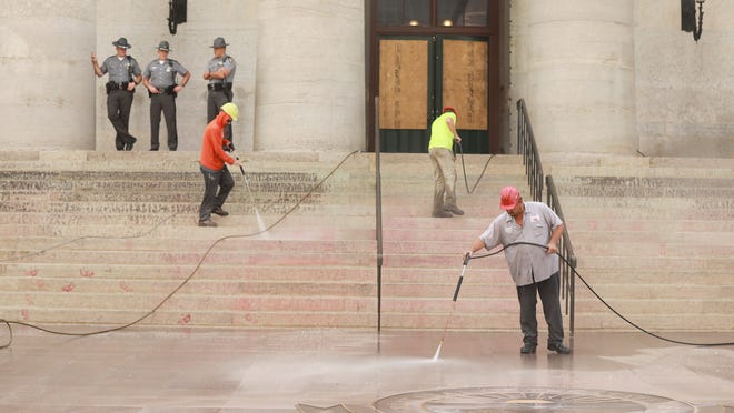 "Men spray off the acrylic paint and spray paint used by George Floyd protesters at the Ohio Statehouse Monday morning, June 22, 2020. The red paint was supposed to be symbolic of how minorities have been victims of police brutality. Prostesters said the intent was to make a statement â€"" not to deface."