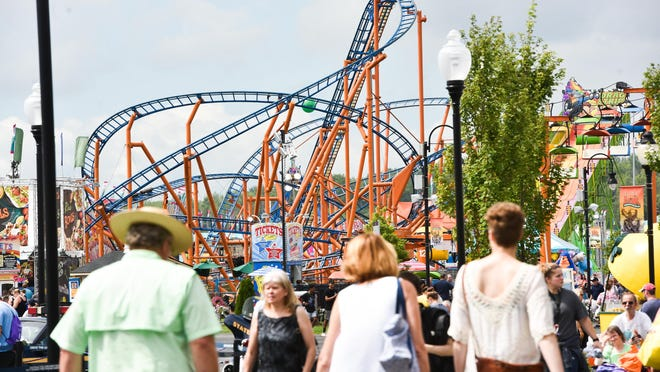 Fair-goers walk around near rides and attractions during opening day at the Great New York State Fair last year in Geddes.