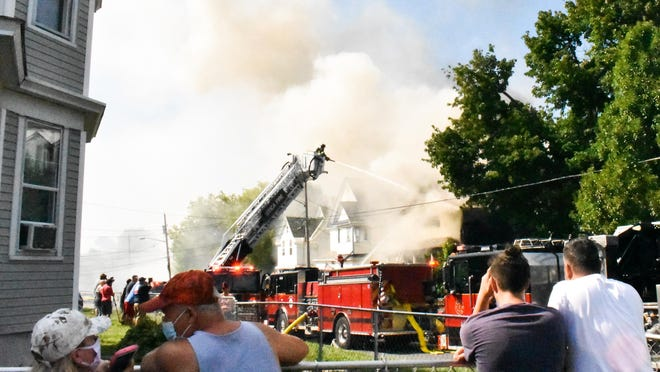 People look on as firefighters battle a blaze Saturday at 1013 Mary Street in Utica.