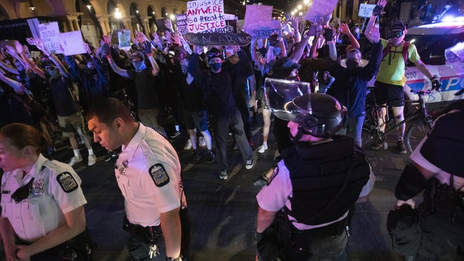Demonstrators stand a few feet from Columbus police officers in a standoff at Goodale Street in the Short North during a protest for racial equality on Friday. Both groups parted ways after a few minutes without incident.